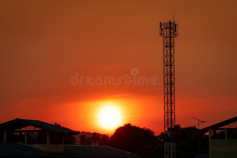 C?u vermelho e alaranjado bonito do por do sol Torre da telecomunicação da silhueta na noite com o céu e as nuvens vermelhos boni fotos de stock royalty free