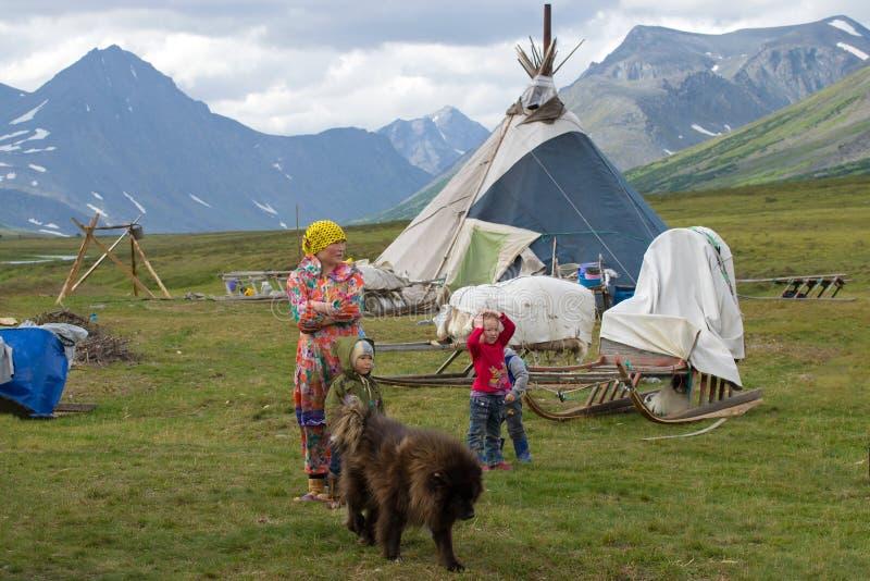 Caça da mulher com crianças em uma rena que reune o acampamento imagens de stock royalty free
