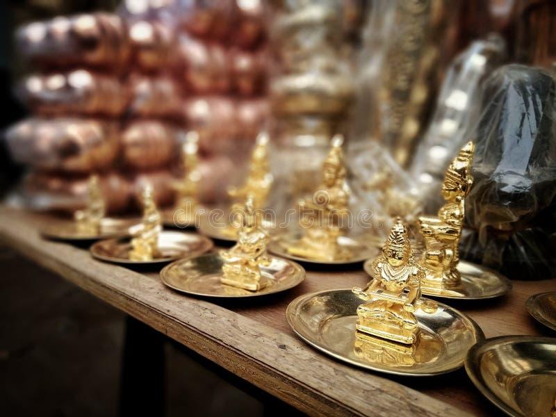 Caça de brasse feita e estátuas de Deus e de deusa douradas revestidas a ouro estão sendo vendidas em Varanasi, Índia imagem de stock