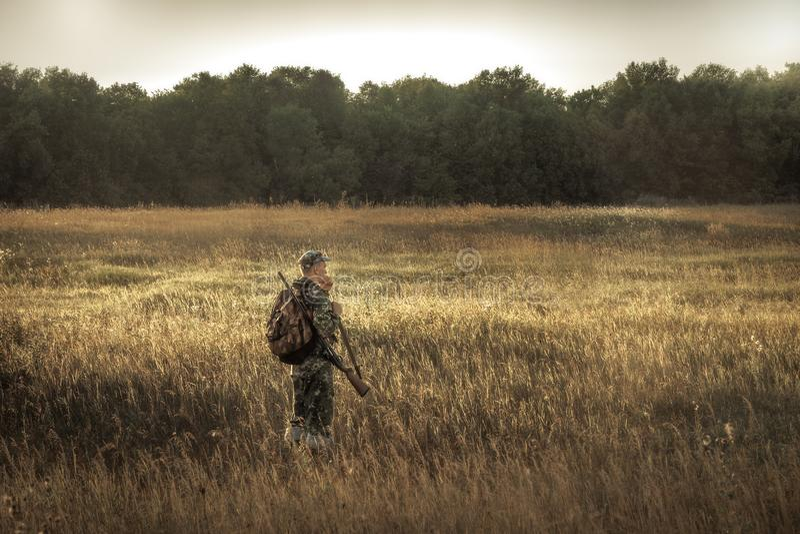 Caça do caçador na floresta próxima do campo rural no por do sol durante a época de caça imagens de stock royalty free