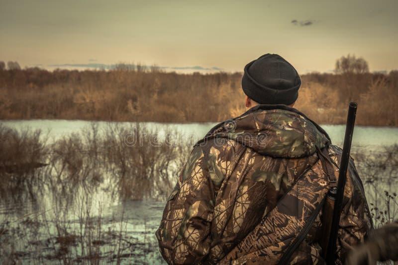 Caça do homem do caçador que olha no horizonte da distância na camuflagem durante a paisagem da inundação do rio do por do sol da fotografia de stock