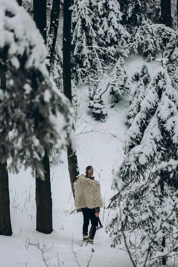 Caçador antigo de viquingue que anda na floresta do inverno da neve com aço a fotografia de stock