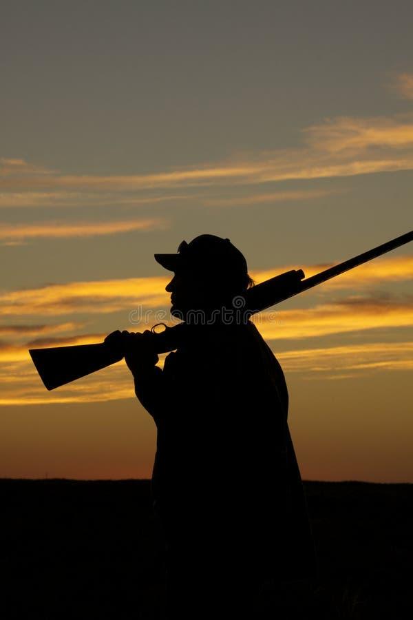 Caçador com a espingarda no por do sol fotografia de stock royalty free