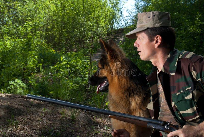 Caçador com o cão no rifle. Emboscada fotos de stock