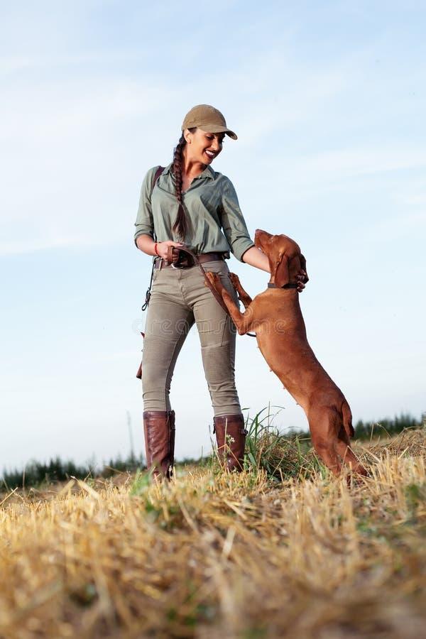 Caçador fêmea bonito com companheiro peludo imagens de stock