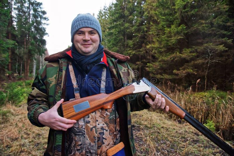 Caçador masculino com a arma ostentando na floresta Báltico do outono foto de stock royalty free
