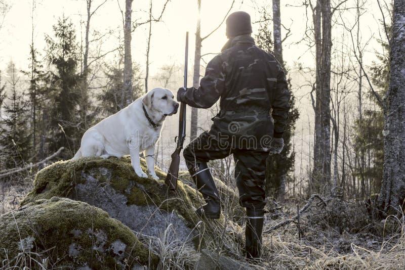 Caçador que olha o nascer do sol na manhã em Finlandia Tem uma espingarda em sua mão e em vestir um uniforme da camuflagem fotografia de stock royalty free