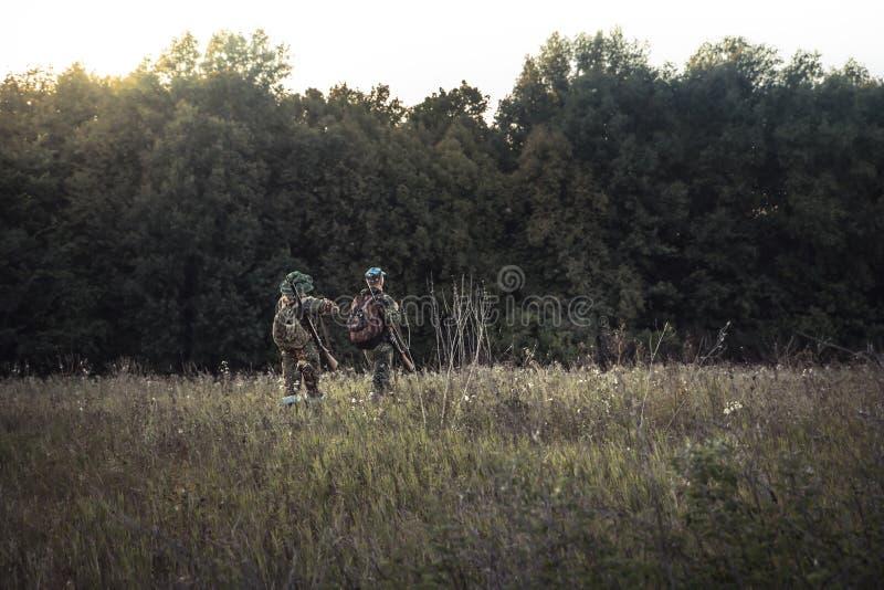 Caçadores da caça na floresta próxima do campo rural no por do sol durante a época de caça fotografia de stock