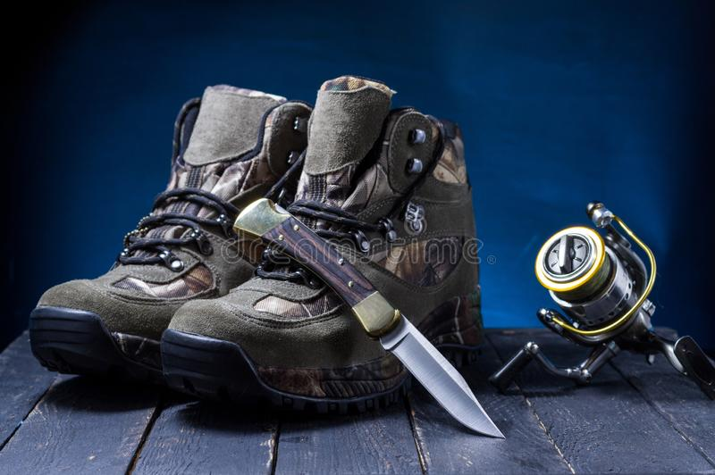 Ca?ando botas, faca e pescando o carretel Sapatas e ca?ador da ferramenta imagem de stock royalty free