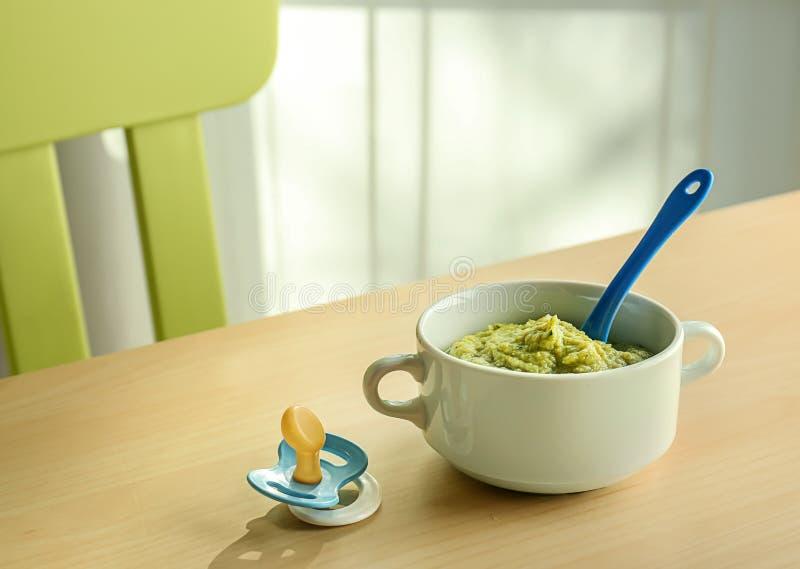 Caçarola com comida para bebê saudável na tabela fotografia de stock