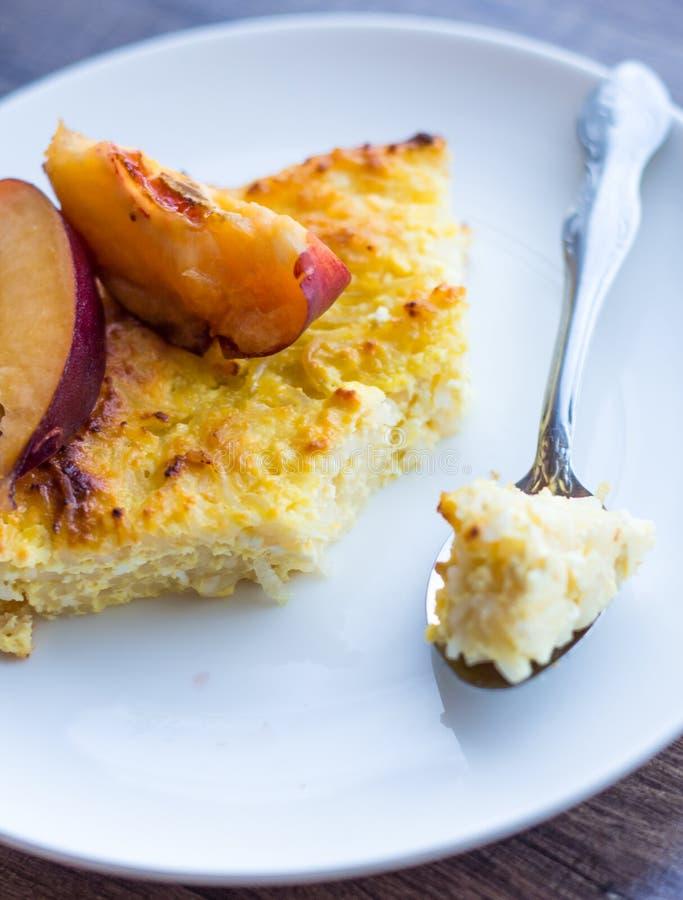 Caçarola doce do requeijão com massa e pêssegos, um teaspoo fotografia de stock