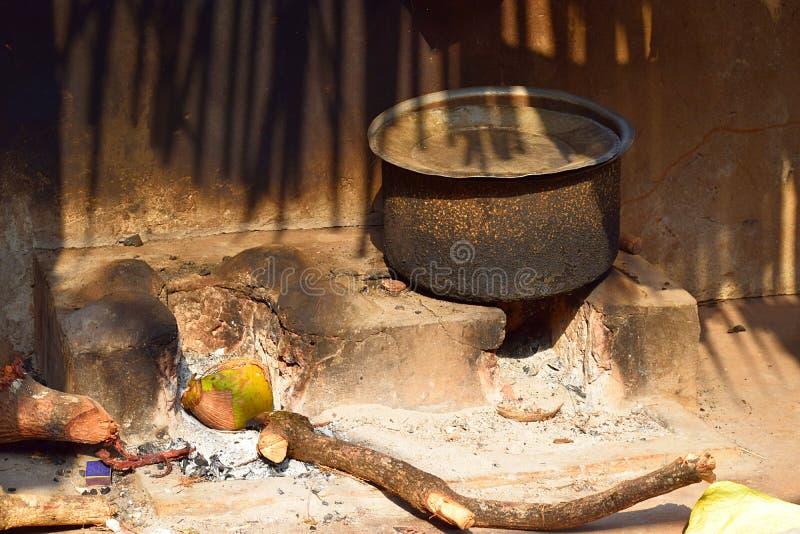 Caçarola na lareira tradicional indiana com vara e a cinza de madeira imagens de stock royalty free