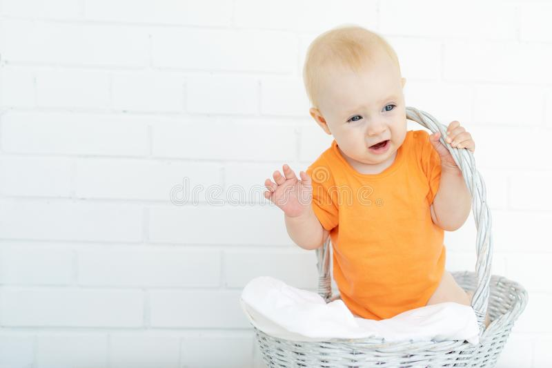 Caçoa está sentando-se na cesta que ri e que acena seus braços e pés fotos de stock royalty free