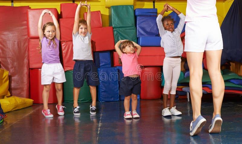 Caçoa a ginástica com as crianças na educação física foto de stock