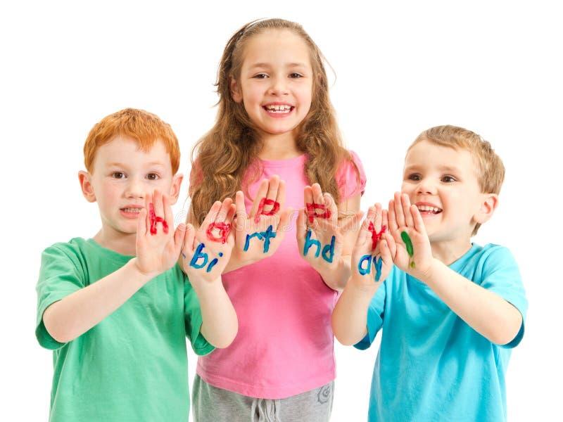 Caçoa letras pintadas do feliz aniversario nas mãos fotografia de stock royalty free