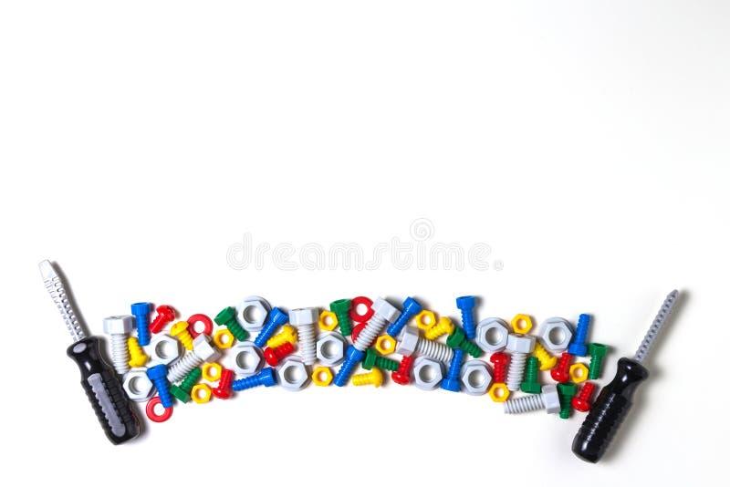 Caçoa o fundo das ferramentas da construção com parafusos plásticos, porcas e chaves de fenda dos brinquedos coloridos fotografia de stock royalty free