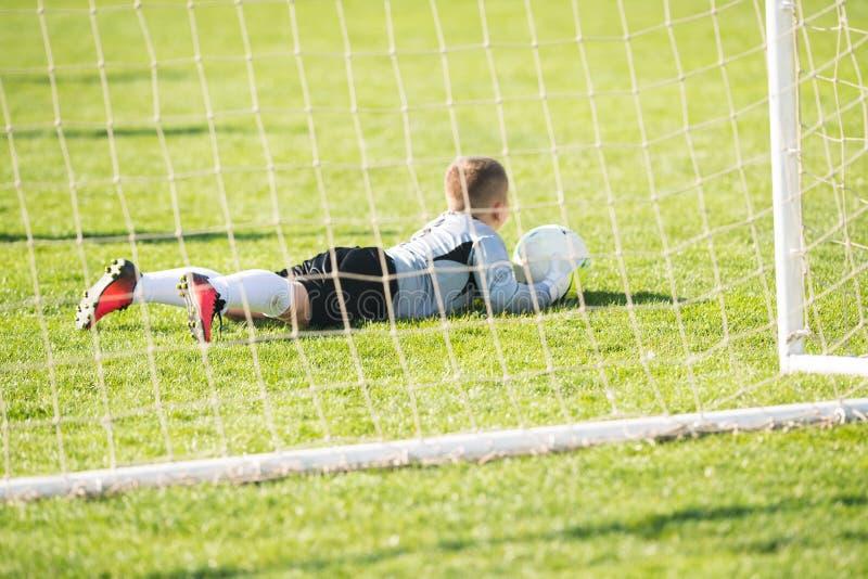 Caçoa o futebol do futebol - depositário do objetivo no fósforo no campo de futebol imagens de stock royalty free