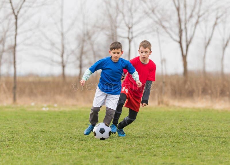 Caçoa o futebol do futebol - os jogadores das crianças combinam no campo de futebol imagem de stock royalty free