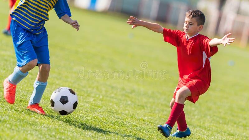 Caçoa o futebol do futebol - os jogadores das crianças combinam no campo de futebol imagens de stock royalty free