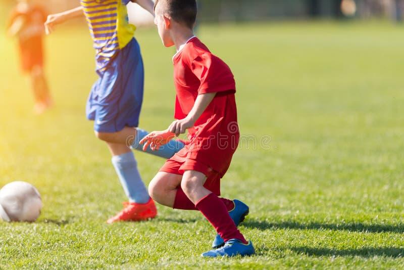 Caçoa o futebol do futebol - os jogadores das crianças combinam no campo de futebol fotos de stock