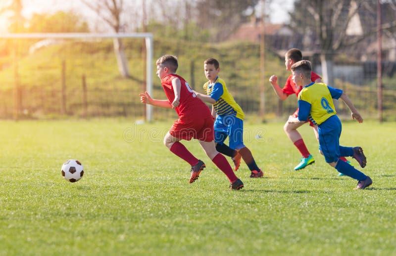 Caçoa o futebol do futebol - os jogadores das crianças combinam no campo de futebol foto de stock royalty free