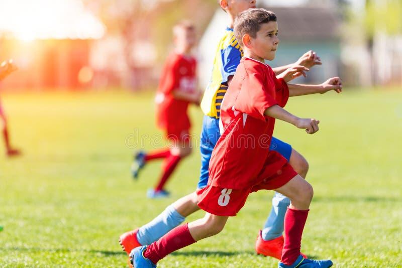 Caçoa o futebol do futebol - os jogadores das crianças combinam no campo de futebol imagens de stock