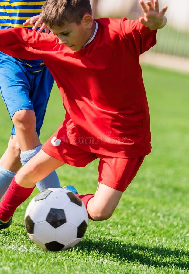 Caçoa o futebol do futebol - os jogadores das crianças combinam no campo de futebol fotografia de stock royalty free