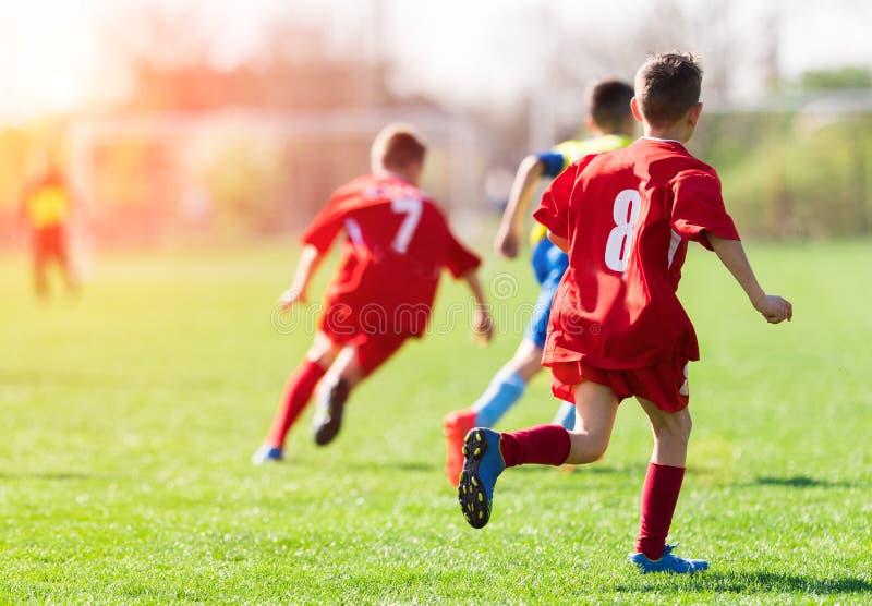 Caçoa o futebol do futebol - os jogadores das crianças combinam no campo de futebol imagem de stock