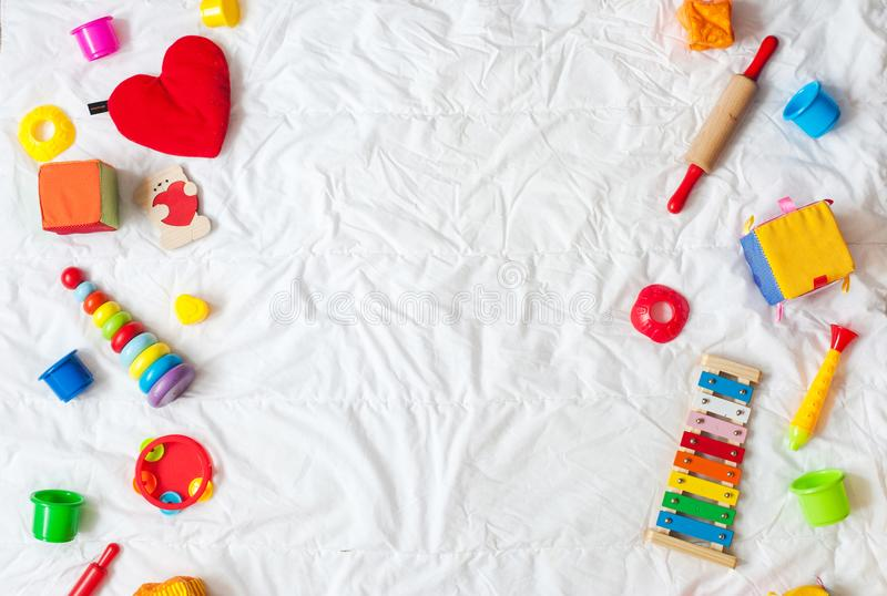 Caçoa o quadro colorido brilhante dos brinquedos no fundo branco Vista superior Configuração lisa Copie o espaço para o texto fotografia de stock royalty free
