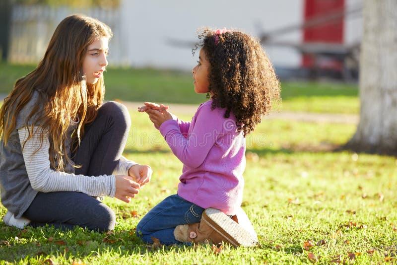 Caçoe as meninas que jogam na afiliação étnica misturada grama do parque fotografia de stock royalty free