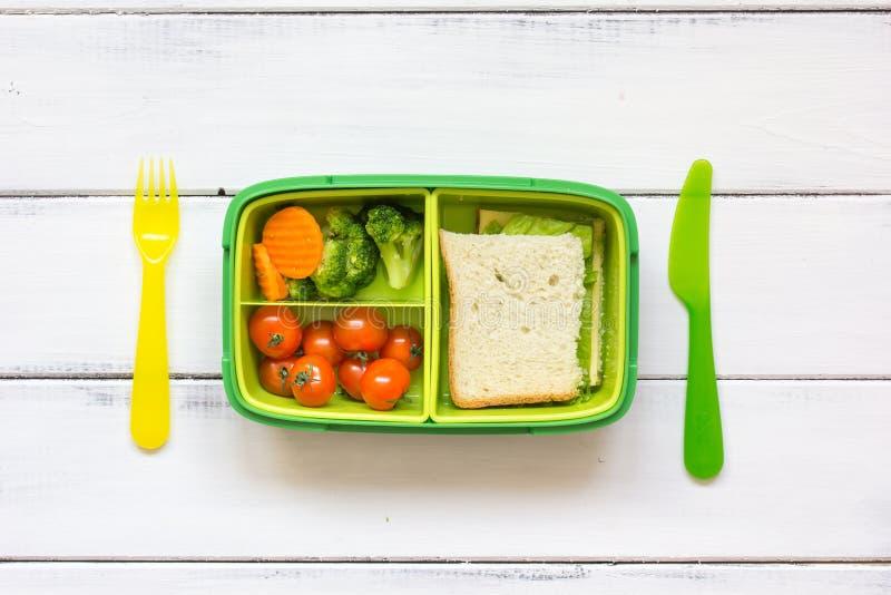 Caçoe a cesta de comida do menu para a opinião superior da escola no fundo de madeira fotos de stock
