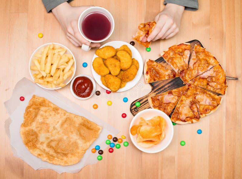 Caçoe comer a pizza, as pepitas, as microplaquetas e o outro fast food Fast food foto de stock