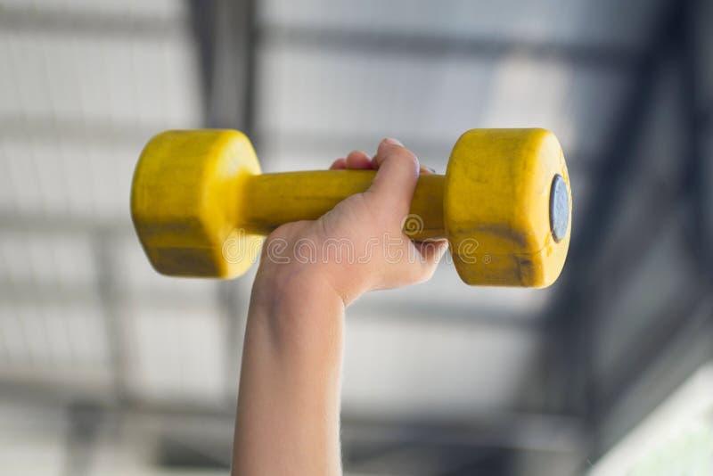 Caçoe dar certo com pesos no salão de esportes do clube Mão da criança que guarda o peso amarelo no fundo verde foto de stock