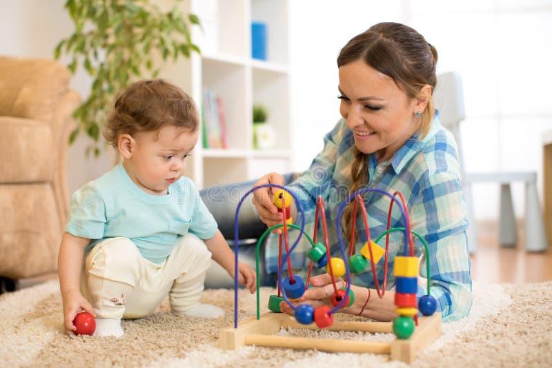 Caçoe e sira de mãe ao jogo com o brinquedo educacional na sala de visitas imagem de stock