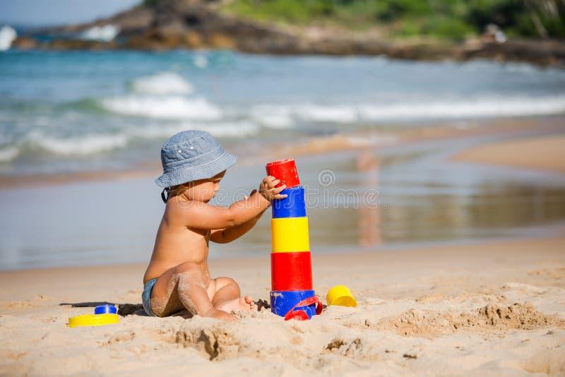 Caçoe jogos com os brinquedos no litoral no verão imagens de stock royalty free
