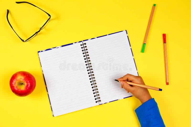Caçoe a mão com caderno aberto, pena, vidros e a maçã fresca no fundo amarelo imagem de stock