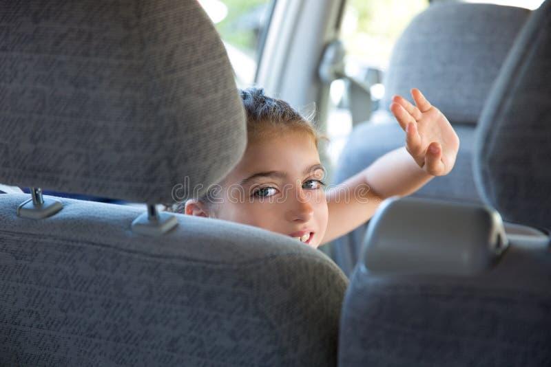 Caçoe a mão feliz do gesto do cumprimento da menina no carro interno fotografia de stock royalty free