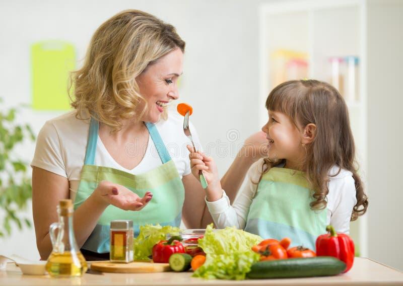 Caçoe a menina e a mãe que comem vegetais saudáveis do alimento fotos de stock