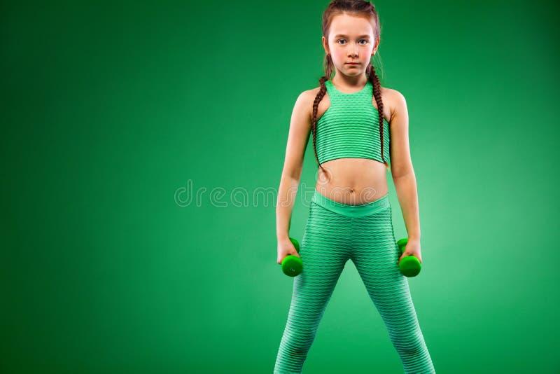 Caçoe a menina que faz exercícios da aptidão com pesos no fundo verde fotografia de stock royalty free