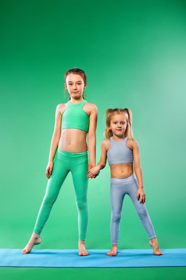 Caçoe a menina que faz exercícios da aptidão no fundo verde imagem de stock royalty free