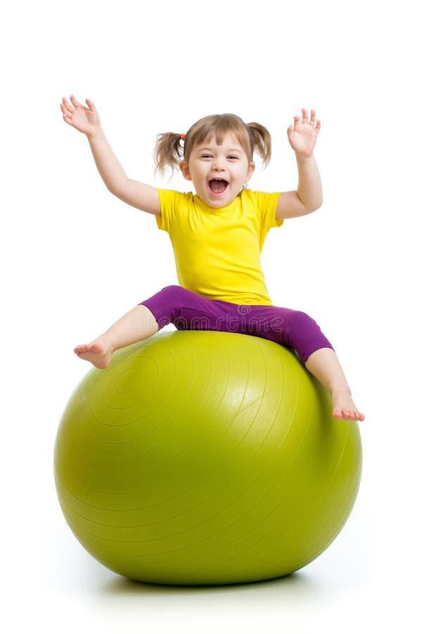 Caçoe a menina que faz a ginástica com a bola isolada no fundo branco imagem de stock