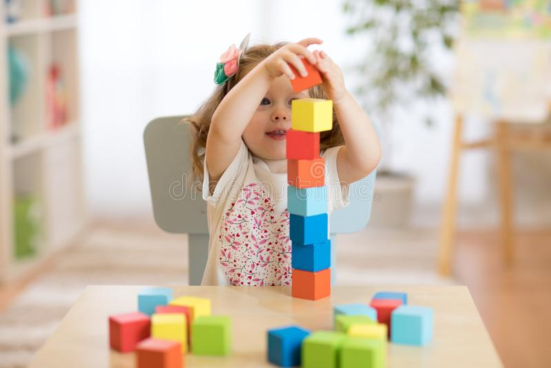 Caçoe a menina que joga com os brinquedos do bloco no centro de centro de dia imagens de stock royalty free