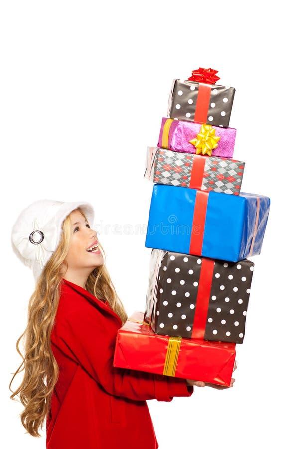Caçoe a menina que mantem muitos presentes empilhados em sua mão foto de stock