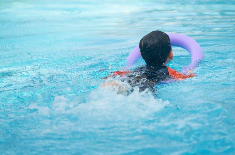 Caçoe a nadada com o macarronete da espuma para aprender a classe da natação na água p foto de stock royalty free