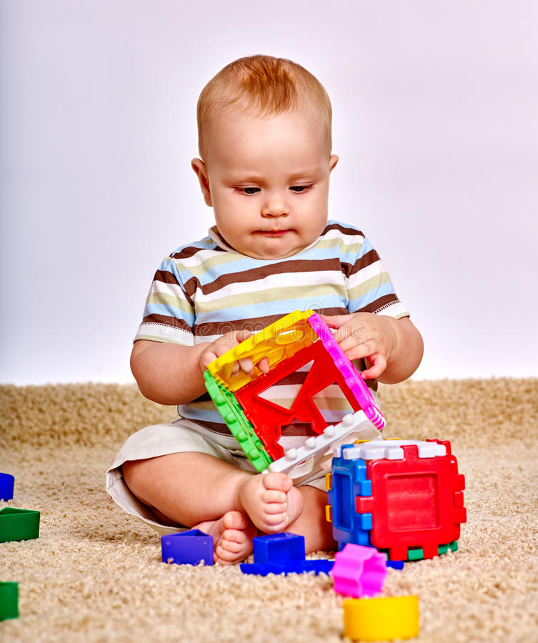 Caçoe o bebê que exerce com o brinquedo do enigma no assoalho fotos de stock royalty free