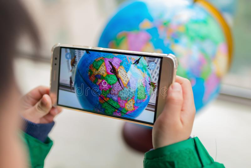 Caçoe o jogo do globo emergente aumentado da realidade com os dinossauros através do móbil foto de stock