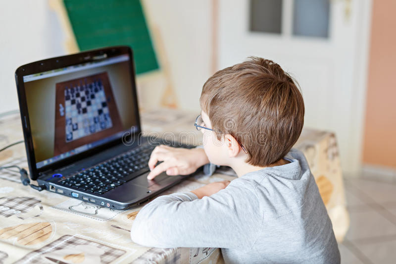 Caçoe o menino com os vidros que jogam o jogo de mesa em linha da xadrez no computador fotografia de stock