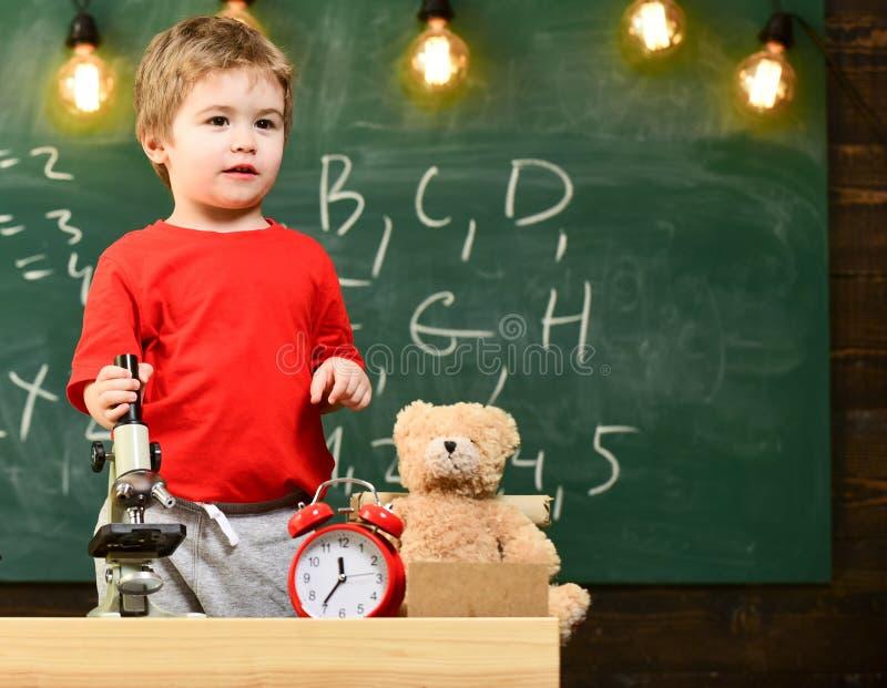 Caçoe o menino perto do microscópio na sala de aula, quadro no fundo Primeiro interessado anterior no estudo, aprendendo, educaçã imagens de stock royalty free