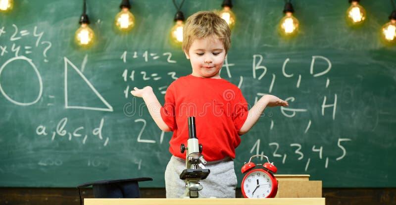 Caçoe o menino perto do microscópio, pulso de disparo na sala de aula, quadro no fundo Primeiro confuso anterior com estudo, apre fotos de stock royalty free