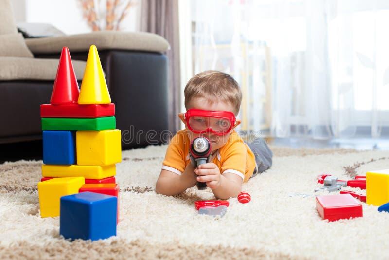 Caçoe o menino que joga com blocos de apartamentos e que imagina-se um herói imagens de stock royalty free